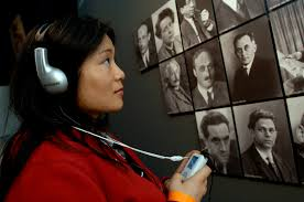 Young lady using a listening device in a museum.
